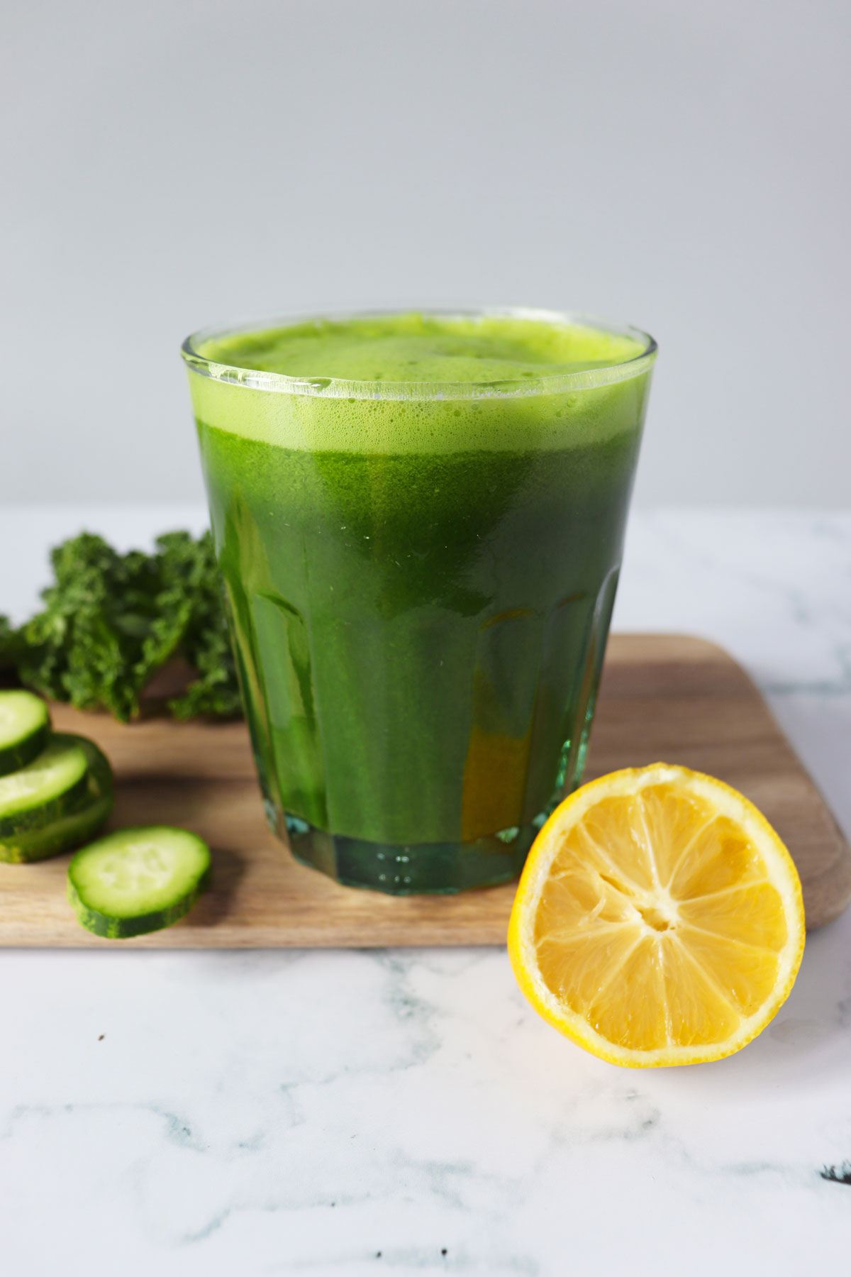 A glass of green juice with cucumber, lemon, and kale